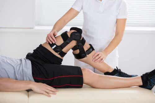 Een fysiotherapeut helpt een man met een knieblessure