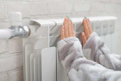 Een vrouw houdt haar handen tegen de verwarming