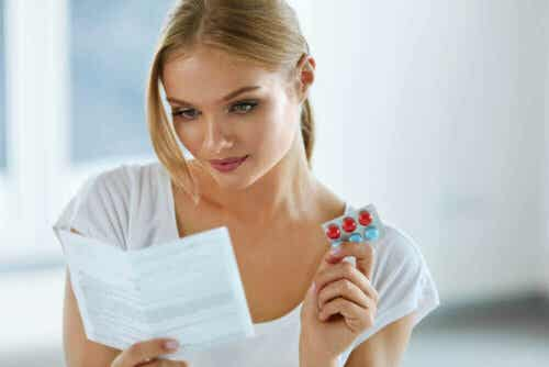 Een vrouw leest de bijsluiter van een medicijn