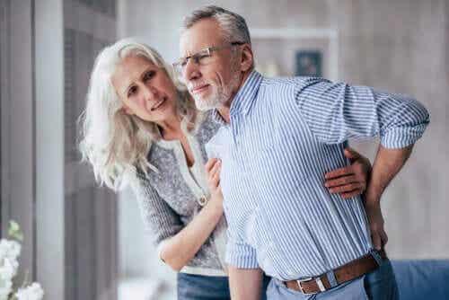 Een oudere vrouw houdt een oudere man overeind, die naar zijn rug grijpt