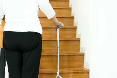 Een oudere vrouw gebruikt een wandelstok om de trap op te lopen