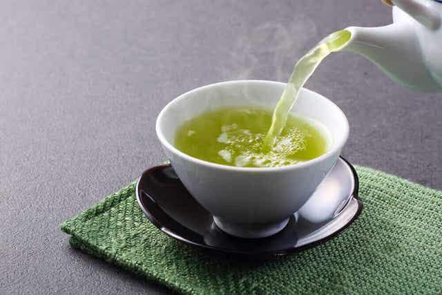 Iemand schenkt een kopje groene thee in