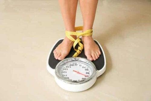 Een vrouw staat op een weegschaal met meetlint rond haar voeten
