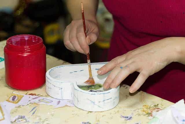 Vrouw decoreert een hartvormig doosje