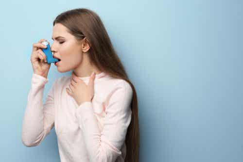Een vrouw met astma gebruikt een inhalator