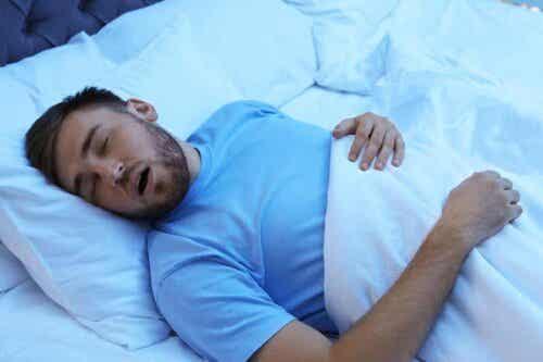Een man slaapt met zijn mond open