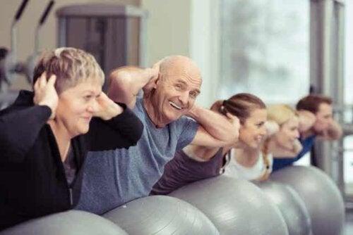 Een ouder echtpaar neemt deel aan een fitnessles