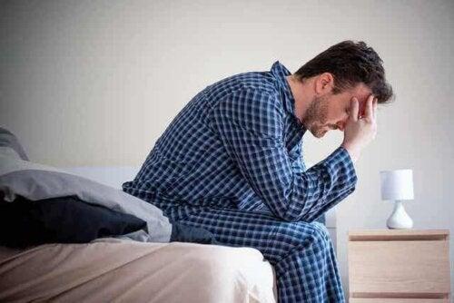 Een man zit op de rand van zijn bed met zijn hoofd in zijn handen